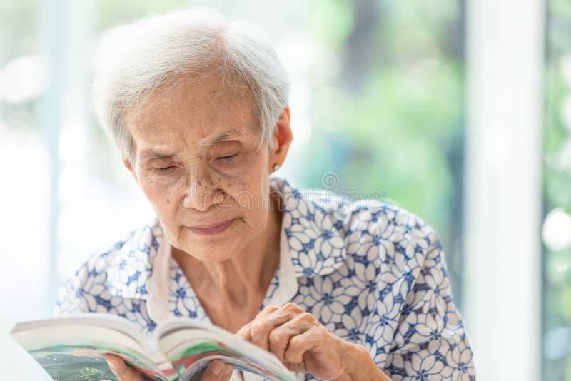 De Aziatische hogere vrouw die een thuis ontspannen boek lezen, bejaarde besteedt hun boek van de vrije tijdlezing stock afbeelding