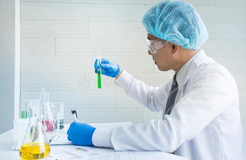 De Aziatische de holdingsbuis van de wetenschapperchemicus met het groene vloeibare chemische oplossing maken test of onderzoek stock foto