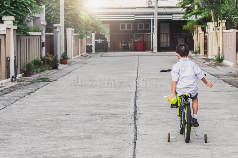 De Aziatische hometrainer van jong geitjestudenten openlucht voor het dorp voor de rit van de levensstijlpret het gelukkige bikin royalty-vrije stock foto's