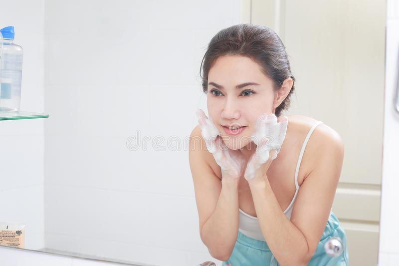 De Aziatische huid van het vrouwen schoonmakende gezicht geniet zich van met bellencleansi stock fotografie