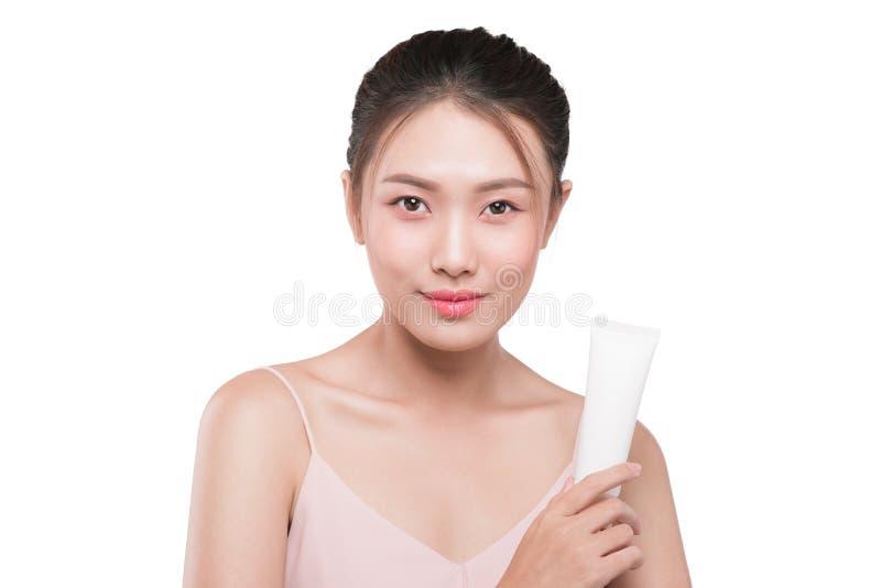 De Aziatische jonge buis van de vrouwenholding vochtinbrengende crème, zonroom stock foto's