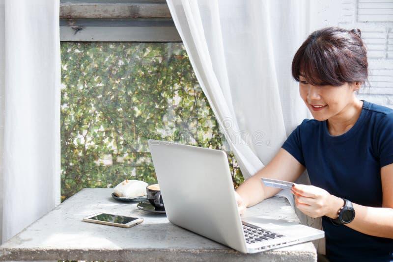 De Aziatische jonge creditcard van de vrouwenholding en het gebruiken van laptop computer terwijl het zitten in koffie Online het royalty-vrije stock foto's