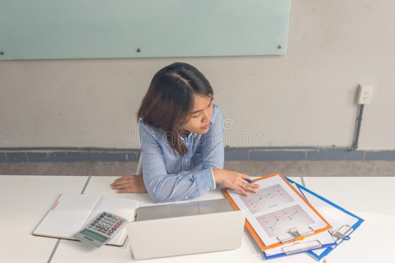 De Aziatische jonge rapporten van de onderneemsterlezing in de bedrijfsruimte stock afbeelding