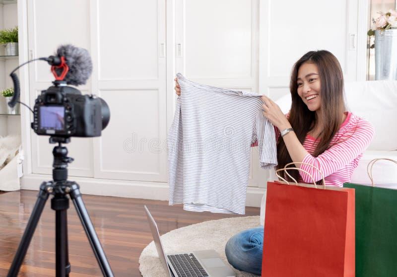 De Aziatische jonge vrouwelijke video van de bloggeropname vlog met de T-shirt thuis online influencer van overzichtsdoeken op so royalty-vrije stock foto