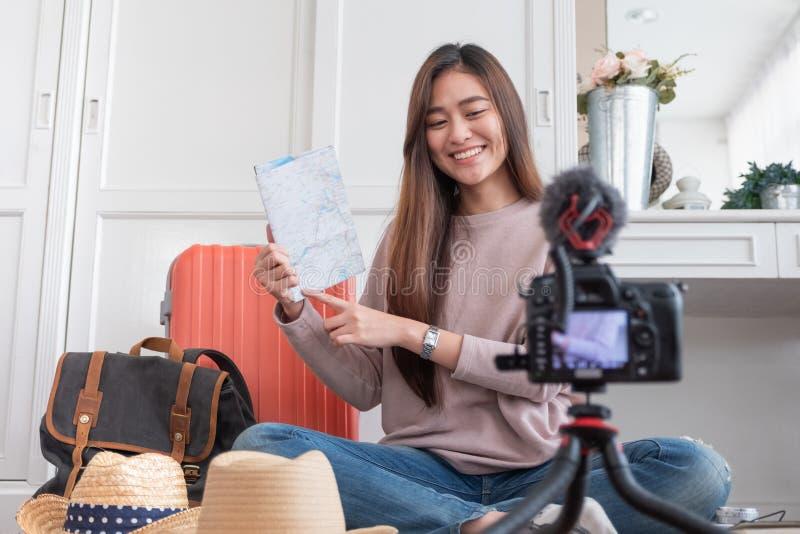 De Aziatische jonge vrouwelijke video van de bloggeropname vlog met vakantie die reis voorbereidingen treffen thuis te reizen onl royalty-vrije stock foto's