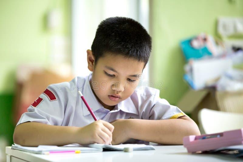 De Aziatische jongen bored is doend zijn thuiswerk stock afbeeldingen