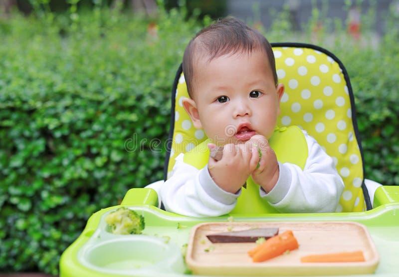 De Aziatische jongen die van de zuigelingsbaby door Baby Geleide Te spenen BLW eten Het concept van het vingervoedsel stock foto