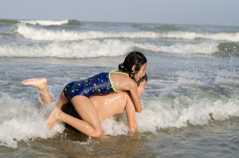 De Aziatische jongen en het meisje genieten van op het strand in zonnige dag royalty-vrije stock foto's