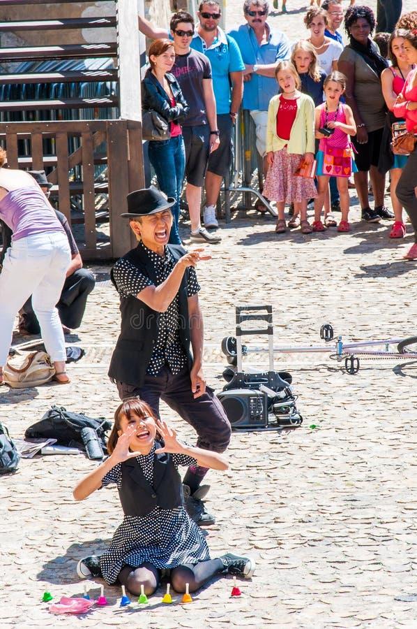 De Aziatische jongen van straatkunstenaars en meisjesjugglers en acrobaten die in Oude Stad van Avignon, Frankrijk tijdens Art Fe royalty-vrije stock afbeelding