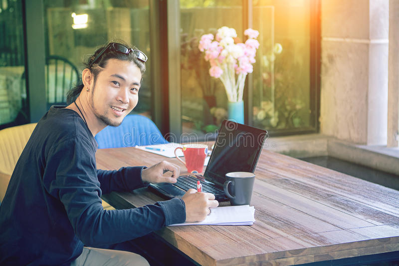 De Aziatische jongere freelance mens die thuis bureau werken met verwerkt gegevens stock foto