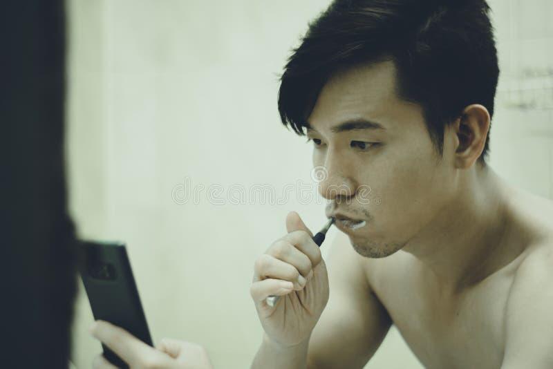 De Aziatische kerel borstelt zijn tanden en las het nieuws op smartphone in de badkamers stock foto
