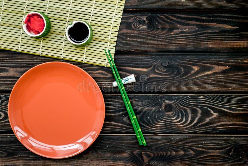 De Aziatische keuken plaatste met bamboe omhoog stokken, plaat, sojasaus en gember voor maki op houten achtergrond hoogste mening stock afbeelding