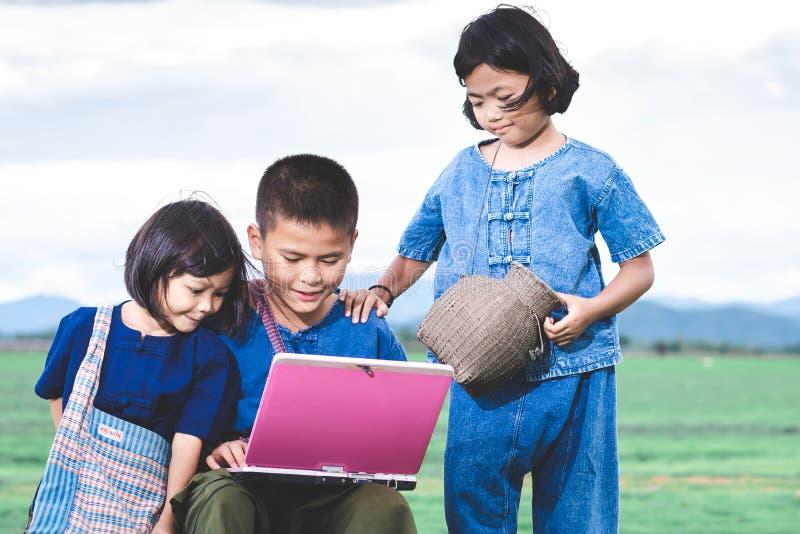 De Aziatische kinderen in lokale kleding gebruiken laptop voor onderwijs en mededeling stock afbeelding