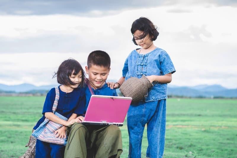 De Aziatische kinderen in lokale kleding gebruiken laptop voor onderwijs en mededeling stock foto's
