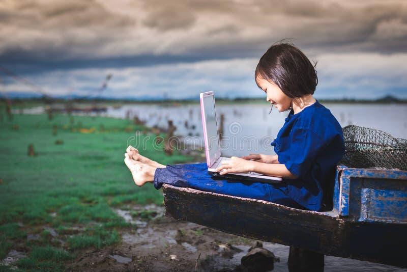De Aziatische kinderen in lokale kleding gebruiken laptop voor onderwijs en mededeling royalty-vrije stock fotografie