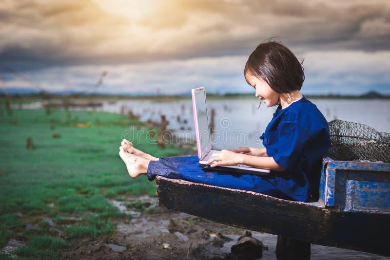 De Aziatische kinderen in lokale kleding gebruiken laptop voor onderwijs en mededeling stock afbeeldingen