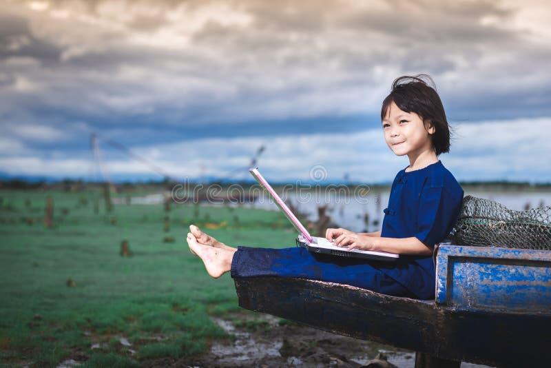 De Aziatische kinderen in lokale kleding gebruiken laptop voor onderwijs en mededeling royalty-vrije stock afbeeldingen