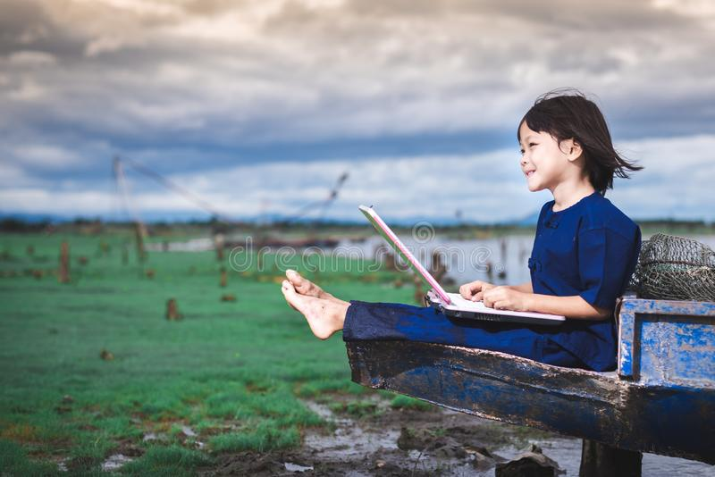 De Aziatische kinderen in lokale kleding gebruiken laptop voor onderwijs en mededeling royalty-vrije stock afbeelding