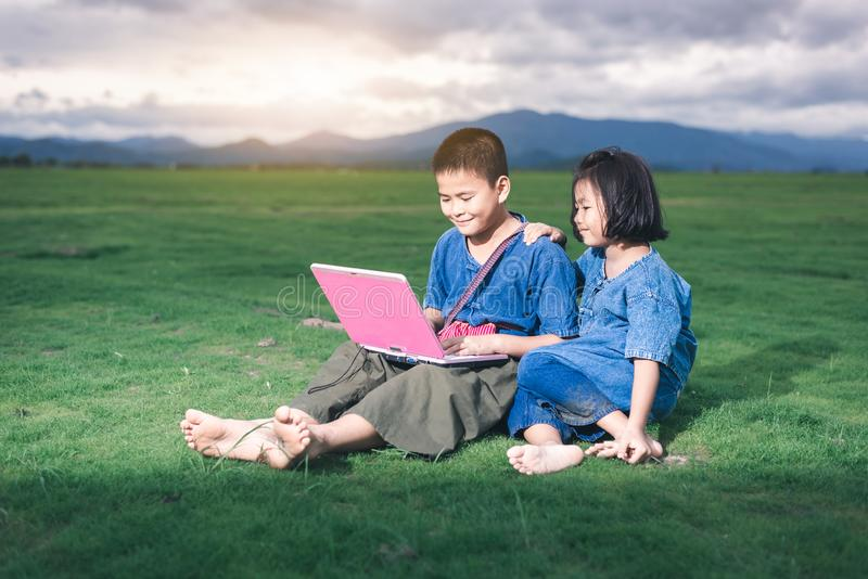 De Aziatische kinderen in lokale kleding gebruiken laptop voor onderwijs en mededeling stock foto