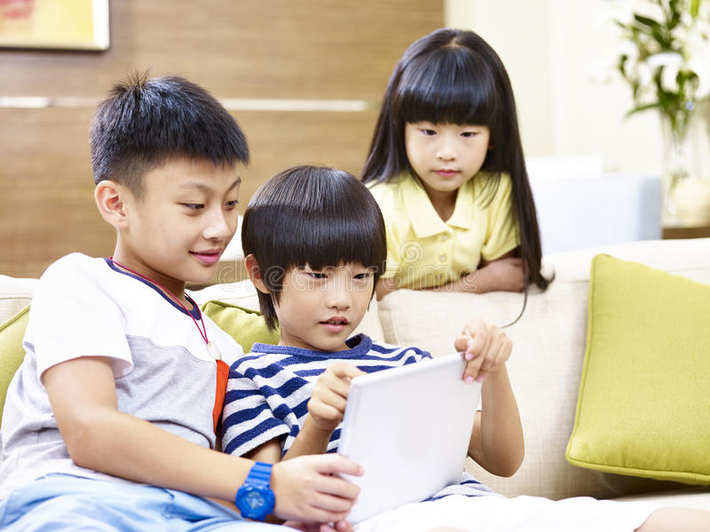 De Aziatische kinderen spelen thuis videospelletje stock afbeeldingen