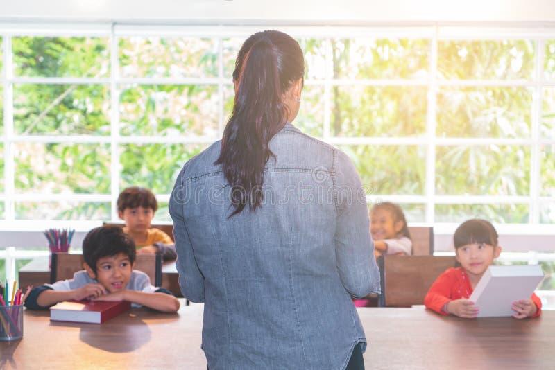 De Aziatische kinderen van het Leraarsonderwijs in klaslokaal royalty-vrije stock afbeelding