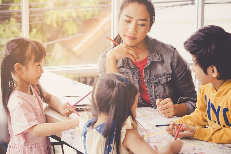 De Aziatische kinderen van het Leraarsonderwijs in kleuterschoolklaslokaal royalty-vrije stock afbeelding