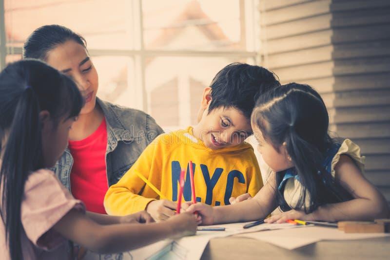 De Aziatische kinderen van het Leraarsonderwijs in kleuterschoolklaslokaal stock foto