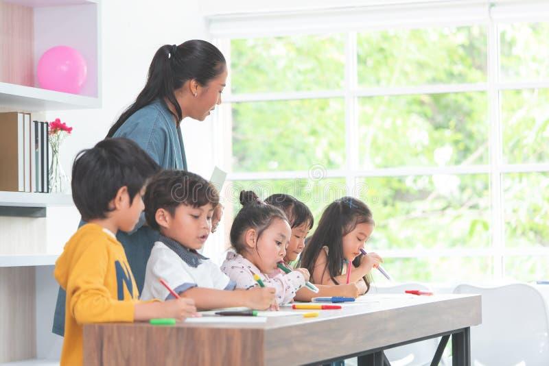 De Aziatische kinderen van het Leraarsonderwijs in kleuterschoolklaslokaal royalty-vrije stock foto's