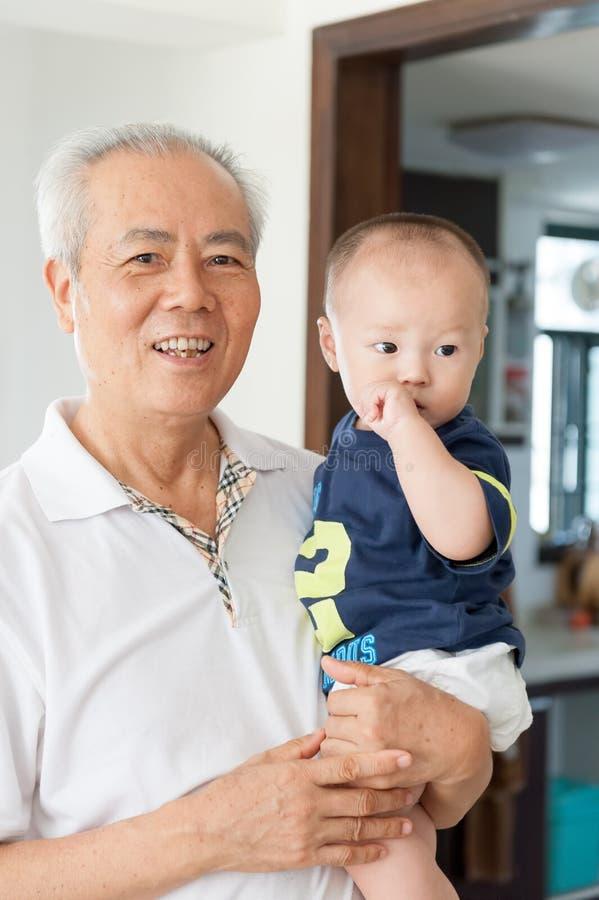 De Aziatische kleinzoon van de grootvaderholding royalty-vrije stock afbeelding