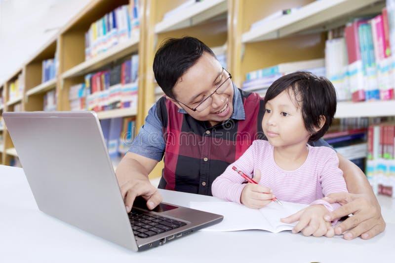 De Aziatische leraar onderwijst vrouwelijke student in bibliotheek stock foto's