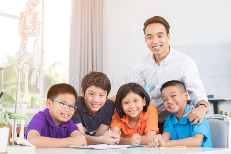 De Aziatische leraar verklaart een menselijk lichaamsstructuur aan weinig leerling stock afbeeldingen