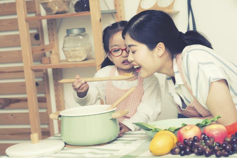 De Aziatische mammavrouw met dochterkok in keuken, de lepel van het meisjegebruik om mamma voedsel-grote zuster te geven en de jo royalty-vrije stock afbeelding