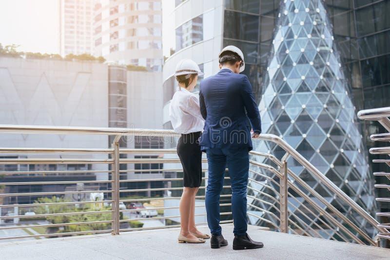 De Aziatische Mannelijke en Vrouwelijke industriële ingenieur een tablet en blauwdrukken houden die werkend en op bouwterrein bes royalty-vrije stock foto's