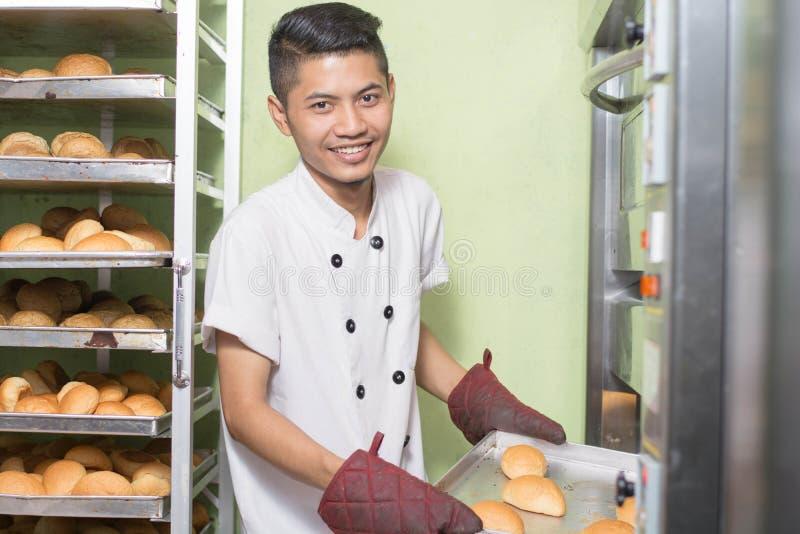 De Aziatische mannelijke gebakjechef-kok bakte zoet brood met grote oven in keuken stock foto's
