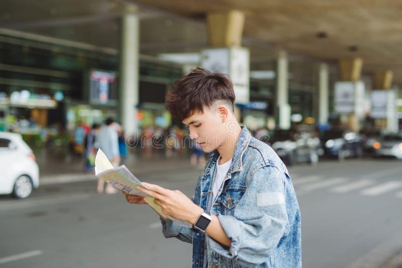 De Aziatische mannelijke kaart van de toeristenlezing terwijl het wachten op taxi bij de lucht stock foto's