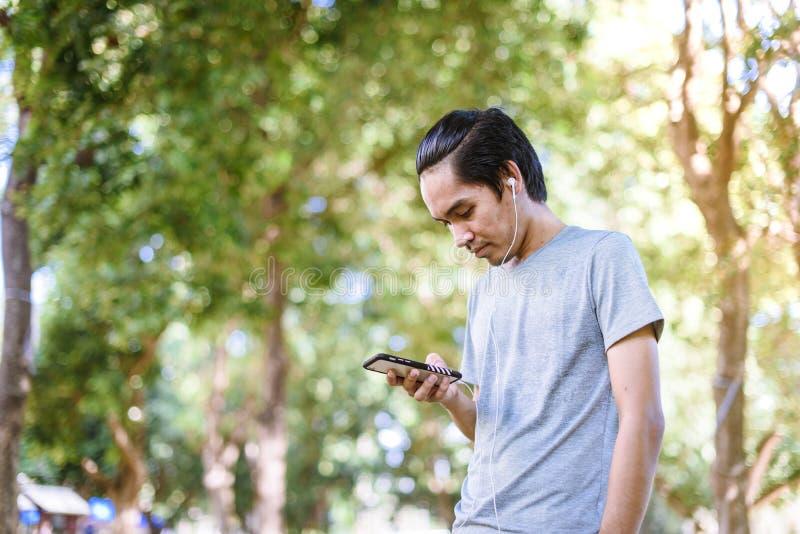 De Aziatische mens heeft rust en luistert aan muziek tijdens in openlucht het lopen stock afbeeldingen