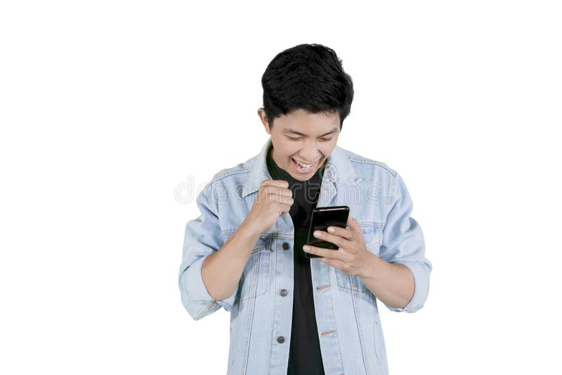 De Aziatische mens krijgt goed nieuws op smartphone stock foto