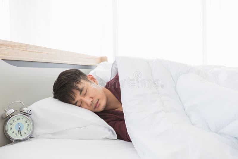 De Aziatische mens ligt aan zijn kant op het bed stock afbeelding