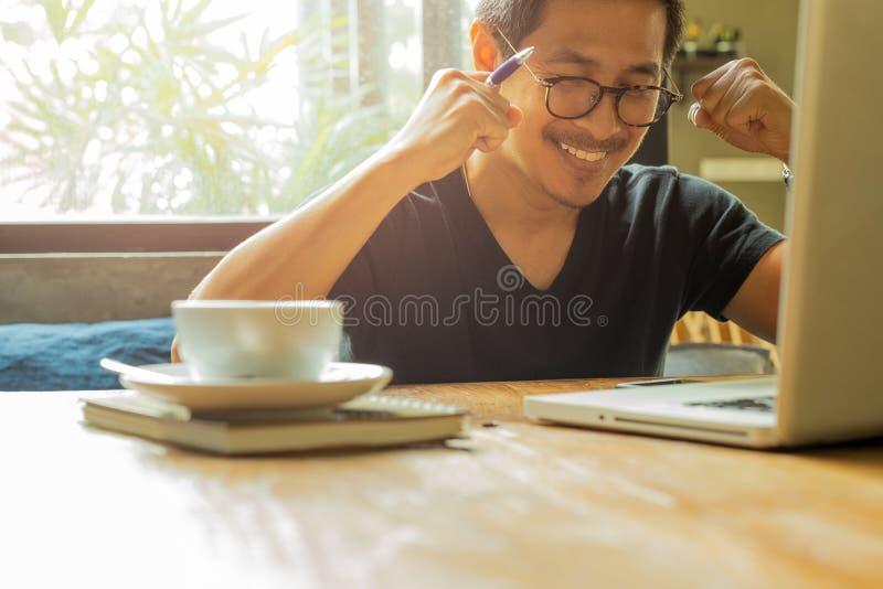 De Aziatische mens met laptop opgeheven handen viert omhoog succes in groot nieuws stock foto