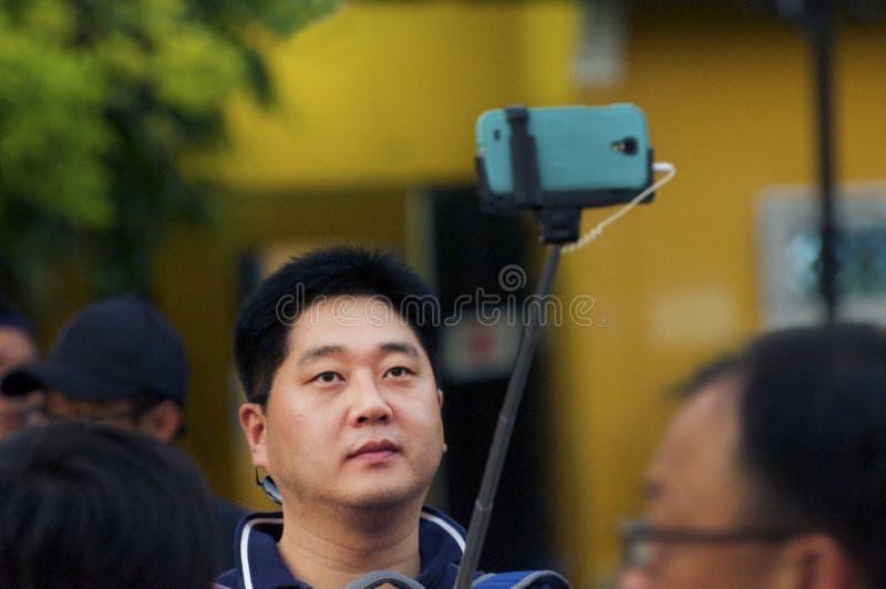 De Aziatische mens neemt selfie met het gebruiken van een stok in de menigte royalty-vrije stock fotografie