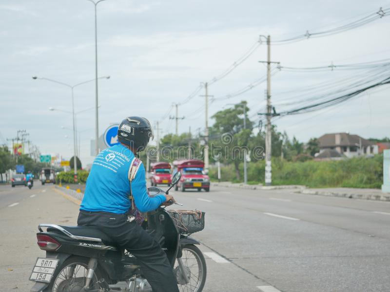 De Aziatische mens op een motor neemt een haastig besluit om een u-Draai in verkeer te maken stock afbeelding