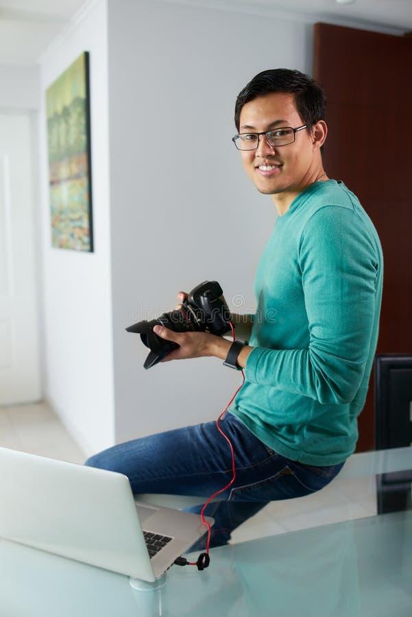 De Aziatische Mens verbindt DSLR met PC-Downloadbeelden op Laptop royalty-vrije stock fotografie