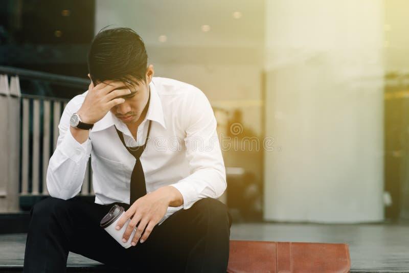 De Aziatische mens zit op de stappen van een bureaugebouw met spanning stock foto's