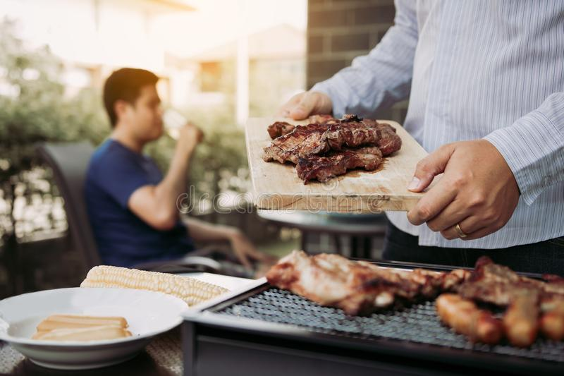 De Aziatische mensen bereiden varkensvlees voor dat op een houten scherpe raad en een holding het aan vrienden wordt geplaatst di stock afbeelding