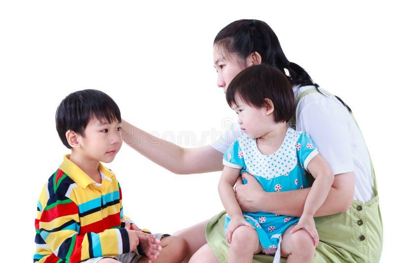 De Aziatische moeder met dochterzitting op overlapping en de zoon voelen slecht Isol stock fotografie