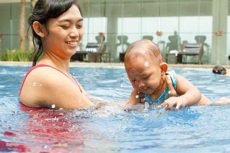 De Aziatische moeder onderwijst baby om te zwemmen royalty-vrije stock afbeeldingen