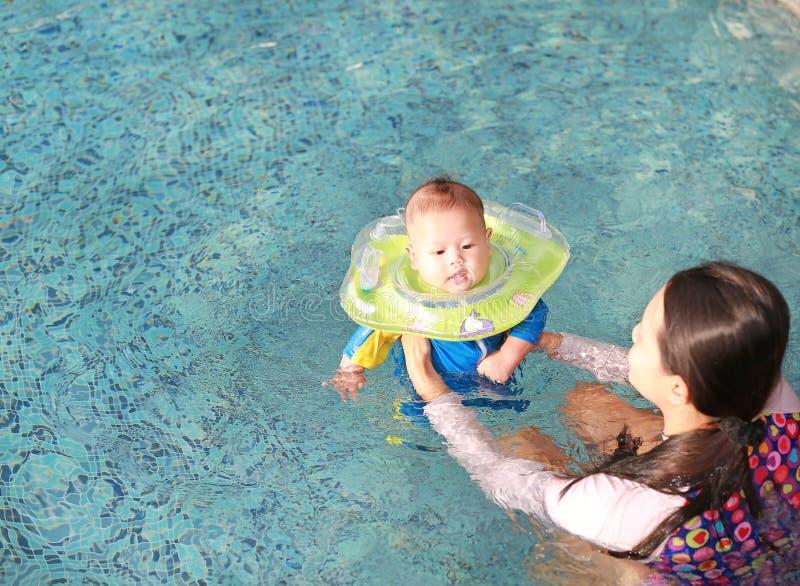 De Aziatische Moeder opleiding voor de jongen van de zuigelingsbaby in zwemmend kostuum die in pool met veiligheid door babyhals  stock foto's