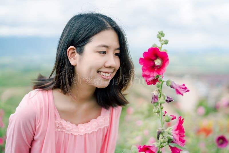 De Aziatische mooie vrouw die een roze overhemd dragen die gelukkig in de roze bloemtuin erachter glimlachen is een bergmening stock foto