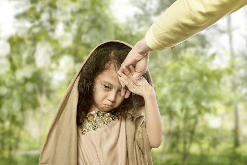 De Aziatische moslimouders van de kind kussende hand voor traditionele handeling van r stock foto's