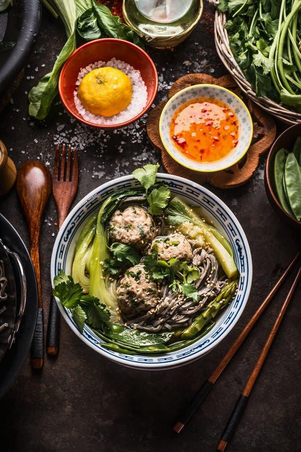 De Aziatische noedels werpen met groene groenten, bok choy en vleesballen op donkere achtergrond met houten bestek, eetstokjes en royalty-vrije stock afbeelding